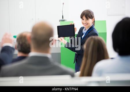 Lächeln, Geschäftsfrau, die Präsentation an die Kollegen vom digitalen Tablette im Hörsaal - Stockfoto