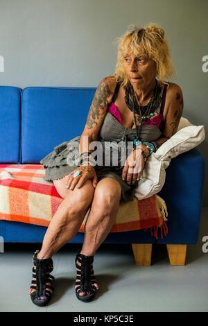 Tilburg, Niederlande. Reifen erwachsenen kaukasische Frau, Porträt, beim Sitzen auf einem Sofa im Wohnzimmer. - Stockfoto