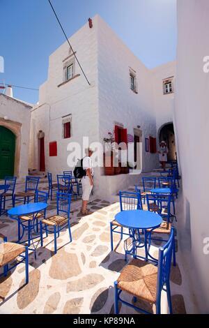 Touristen zu Fuß durch die Tische und Stühle von einem traditionellen Cafe in der Altstadt Chora, Amorgos, Kykladen - Stockfoto