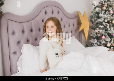 Portrait von niedlichen Lustige kleine Mädchen am Weihnachtsmorgen in Weiß Home Interior. Kind fröhlich in Bett - Stockfoto