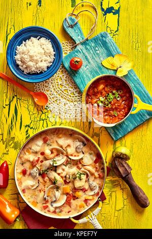 Hohe Betrachtungswinkel von schmackhaften Fisch Suppe oder Soße in Gelb Pan und serviert am Tisch mit Reis und Garnieren - Stockfoto