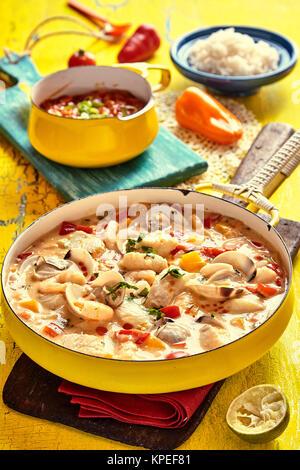 Nahaufnahme von schmackhaften Fisch Suppe oder Soße in Gelb Pan und serviert am Tisch mit Reis und Garnieren - Bunte - Stockfoto