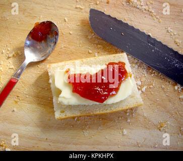 Brot, Butter und Erdbeermarmelade auf einem Teller für Ihren gesunden und vitalen Frühstück platziert - Stockfoto