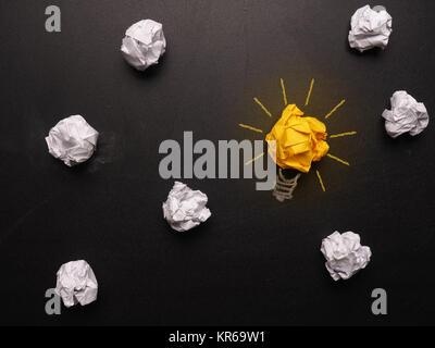 Zerknittertes Papier auf einer Schiefertafel mit einer Glühbirne - Stockfoto