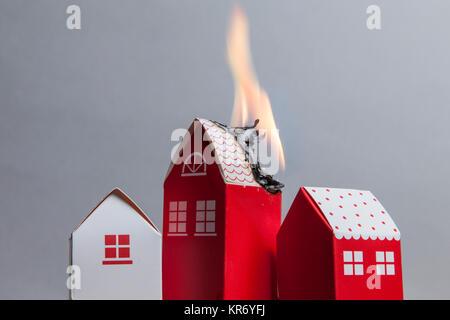 Haus Feuer Konzept. Spielzeug Haus mit Flammen - Stockfoto