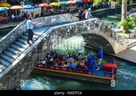 Touristenboot gehen unter der Brücke am San Antonio River entlang dem Riverwalk, San Antonio, Texas USA - Stockfoto