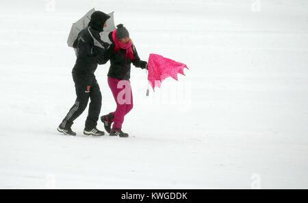 Oberstdorf, Deutschland. 03 Jan, 2018. Zuschauer zu Fuß durch den Schnee am stürmischen und regnerischen Wetter - Stockfoto