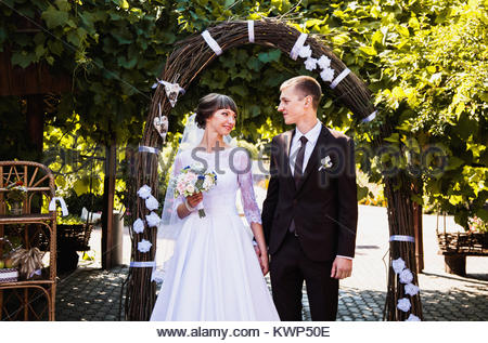 Bräutigam und Braut im weißen Kleid auf dem Hintergrund der Arch. Trauung. Glückliche Familie - Stockfoto