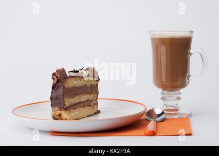 Stück Biskuit mit Schokoladencreme auf weissen Teller, Tasse Kaffee, orange Serviette, auf weißem Hintergrund - Stockfoto