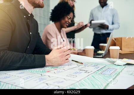 Nahaufnahme eines männlichen Designer arbeiten auf ein Konzept an einem Schreibtisch in einem modernen Büro mit - Stockfoto