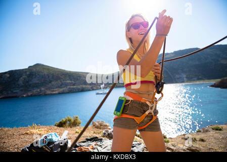 Lächelnd weibliche Kletterer ständigen tragen Kletterausrüstung, Kalymnos, Griechenland - Stockfoto