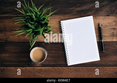 Kaffee, Gläser Kugelschreiber, grüne Pflanze und leeren Notebook auf Holztisch. Flach Top View - Stockfoto
