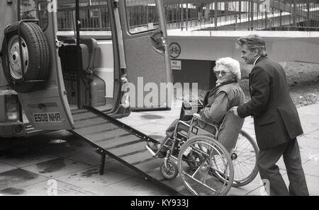 1980 s, historische, alte Dame im Rollstuhl geschoben, eine Rampe in einem Minivan als Teil der Communicare Service - Stockfoto