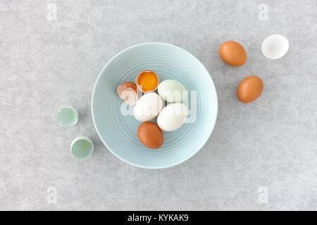 Blaue Eier, braune Eier und Ente, Eier, ganz und halbiert, in einem Pastell-blaue Schüssel auf Grau strukturierten - Stockfoto