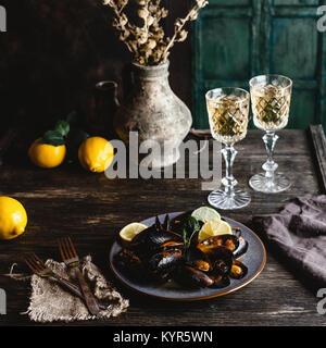 Gekochte Miesmuscheln mit Muscheln auf Platte mit zwei Gläser Weißwein auf hölzernen Tisch serviert - Stockfoto