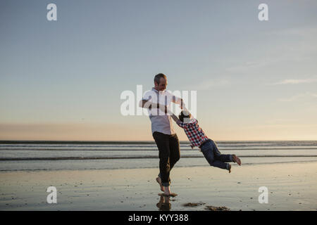 Sorglosen Vater spinnen Sohn am Strand gegen Himmel und Meer bei Sonnenuntergang - Stockfoto