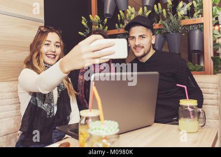 Fröhliche Gruppe von Freunden, ein Mann und zwei Frauen am Tisch sitzen im Cafe Shop, reden, Spaß haben, lachen, - Stockfoto