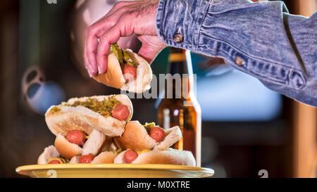 Ein Bachelor man Fernsehen und essen Hot Dogs. - Stockfoto