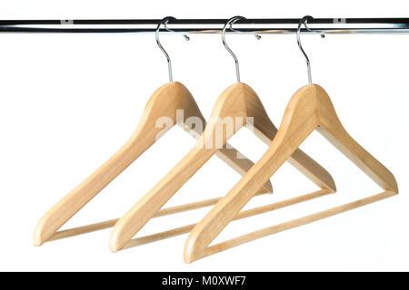 Drei Holz- Mantel-/Kleiderbügel auf einer Kleiderstange mit einem weißen Hintergrund. Mögliche Kopie Raum auf der - Stockfoto