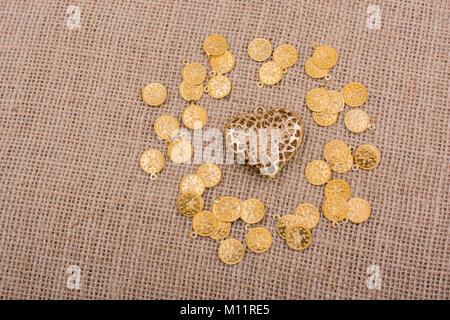 Gefälschte Goldmünzen um Gold Farbe Herz - Stockfoto