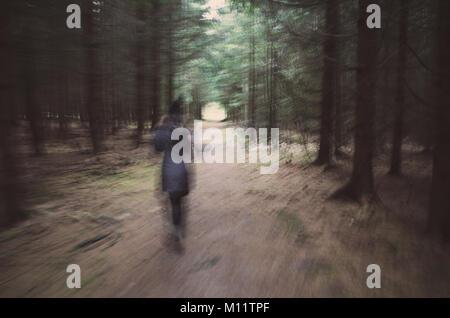 Verschwommenes Bild der Frau im Wald - Stockfoto