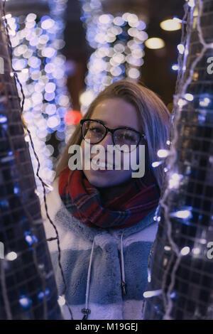 Junge attraktive Mädchen in Gläsern ist zu Fuß in die Stadt. Sie lächelt. Porträt bei Nacht unter Girlanden. - Stockfoto