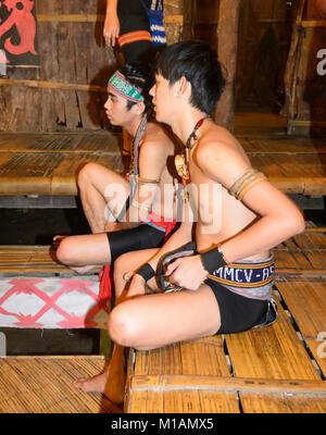 Junge bornesischen Männer tragen tribal Dekorationen in einem traditionellen Langhaus, Mari Mari Cultural Village, - Stockfoto