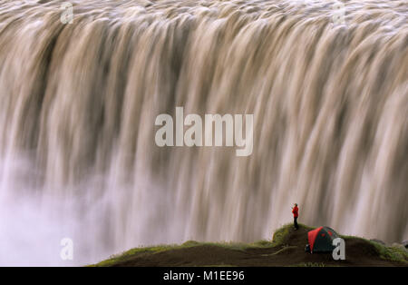 Island. Myvatn. Wasserfall Dettifoss. Touristen, stehende Frau von Zelt am Wasserfall. - Stockfoto