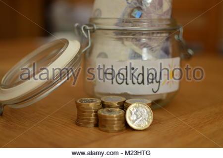Neue ein Pfund Münzen vor Glas Glas mit Urlaub auf White Label mit Geld Notizen in schriftlicher gestapelt. - Stockfoto