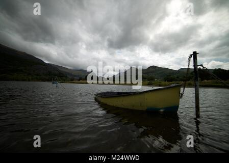 Gelbe Paddel aus Holz Boot gefesselt auf einem See in Snowdonia National Park, mit einem bewölkten Himmel Overhead - Stockfoto