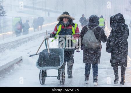 Moskau, Russland. 5. Februar, 2018. Ein Arbeitnehmer (L) entfernt Schnee in einem Park in Moskau, Russland, April - Stockfoto