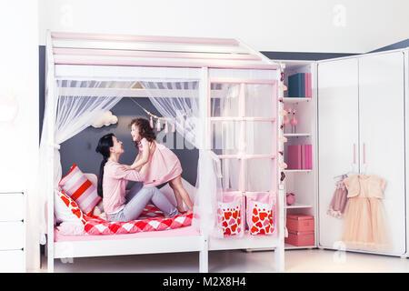 Süße kleine Mädchen und ihre Mutter spielen im Schlafzimmer - Stockfoto
