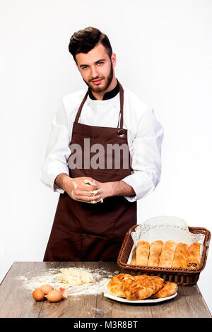 Ein Mann in einer Schürze bereitet den Teig für Backen, Kochen Modell auf einem weißen Hintergrund knetet Teig auf - Stockfoto