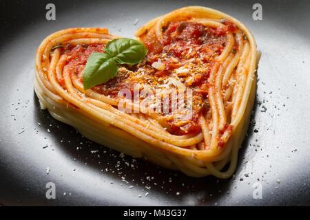 Spaghetti pasta Herz Liebe italienisches Essen Diät abstrakte Konzept auf schwarzem Hintergrund - Stockfoto