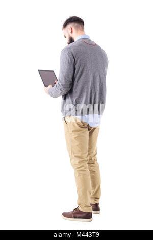 Ansicht der Rückseite des eleganten bärtigen Geschäftsmann mit Tablet pad Computer. Voller Körper Länge Porträt - Stockfoto