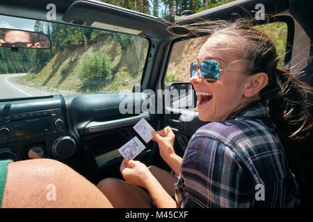Junge Frau auf Straße Reise mit Freund an Instant Foto, Breckenridge, Colorado lachen, USA - Stockfoto