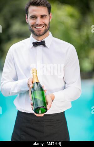 Porträt von lächelnden Kellner Holding Champagner Flasche - Stockfoto