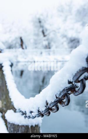 alten rostigen Eisenkette auf dem Frost mit Schnee bedeckt - Stockfoto