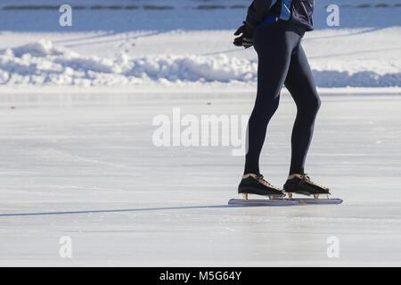 Der Mann Beine auf den Skates ice Ring - Winter Sport an einem sonnigen Tag - Stockfoto