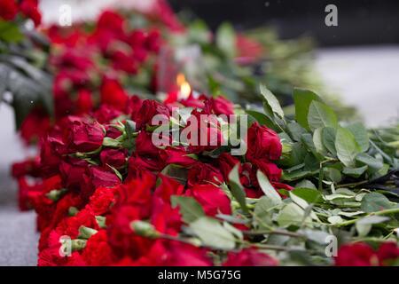 Gartennelke-blumen Symbol der Trauer - Kerze im Wind und rote Blume auf dem Denkmal, in der Nähe - Stockfoto