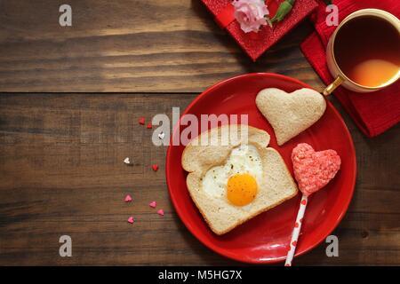 Valentines Tag Frühstück spiegelei Herzform ei Brot Toast Kaffee in rot Teller serviert, Ansicht von oben - Stockfoto