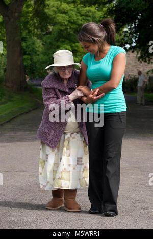 Multikulturelle junge Frau Pfleger mit geriatrischen Dame im Park - Stockfoto