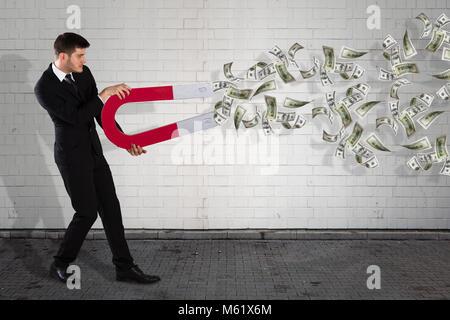 Junge Unternehmer mit Magnet für Banknote Gelder - Stockfoto