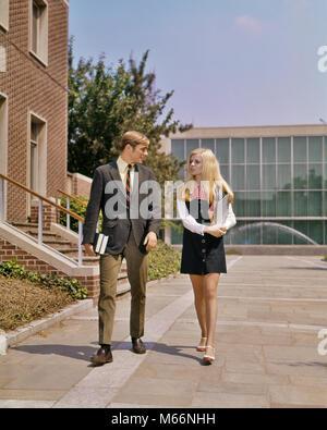 1960er Jahre 1970er Jahre junger erwachsener Schüler PAAR SEITE AN SEITE AUF DEM CAMPUS MÄDCHEN IN MINIKLEID JUNGE - Stockfoto