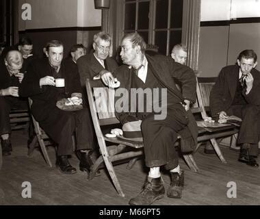 Während der großen Depression der 30er Jahre arbeitslose Männer sitzen im Zimmer auf HOLZSTÜHLEN, trinken Kaffee - Stockfoto