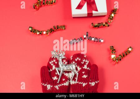 Weibliche Hände halten Weihnachten Reh in rot Handschuhe - Stockfoto