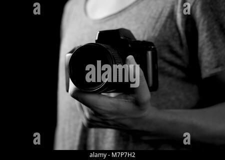 Nahaufnahme eines jungen kaukasischen Mann mit einer Spiegelreflexkamera in der Hand, in Schwarz und Weiß - Stockfoto