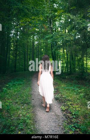 Zurück Blick auf eine junge brünette Frau, die in einem eleganten, weißen Kleid bekleidet, zu Fuß auf den Weg durch - Stockfoto