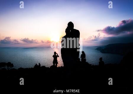 Menschen beobachten Sonnenuntergang am Strand. Zurück Blick auf ein paar silhouette Sonne beobachten bei Sonnenuntergang - Stockfoto