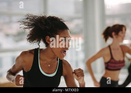 Intensive Fitness Training in der Turnhalle. Frau mit voller Stärke in der Klasse im Health Club. - Stockfoto
